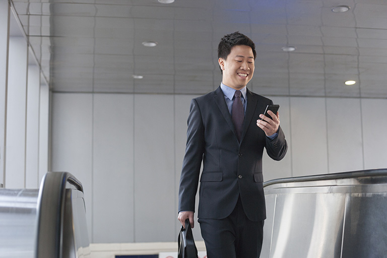 Businessman looking at phone while walking